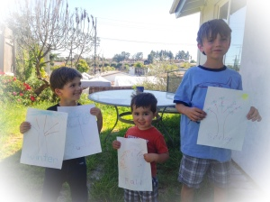 kids show off their pictures of trees on a spring day